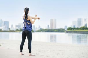 都市のビーチでヨガをする若い女性の写真素材 [FYI04840669]