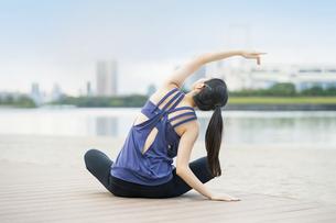 都市のビーチでヨガをする若い女性の写真素材 [FYI04840675]