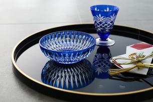 黒の丸盆に乗った切子のグラスと切子の小鉢の写真素材 [FYI04840763]