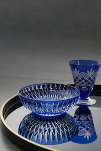 黒の丸盆に乗った切子のグラスと切子の小鉢の写真素材 [FYI04840765]