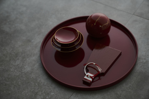 赤い丸盆の上の赤い杯と羽子板型のプレートに丸い容器の写真素材 [FYI04840766]