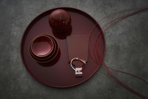 赤い丸盆に乗った杯と羽子板型のプレートと丸い容器に水引きの写真素材 [FYI04840768]