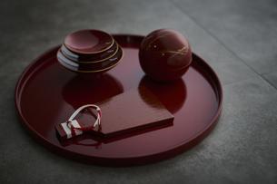 赤い丸盆に乗った杯と羽子板型のプレートと丸い容器に水引きの写真素材 [FYI04840771]