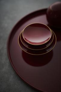 赤い丸盆に乗った杯と丸い容器の写真素材 [FYI04840772]