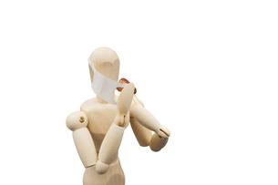 マスクを片方だけ開けて肉を食べるデッサン人形の写真素材 [FYI04840938]