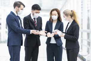 除菌スプレーを使うビジネスチームの写真素材 [FYI04841217]