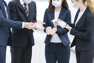 除菌スプレーを使うビジネスチームの写真素材 [FYI04841218]