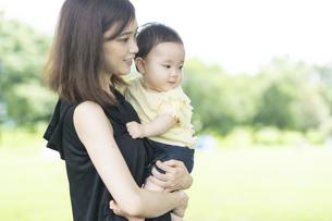 公園で赤ちゃんを抱っこするお母さんの写真素材 [FYI04841238]