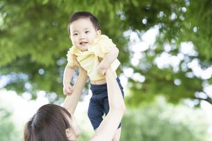 公園で赤ちゃんを抱っこするお母さんの写真素材 [FYI04841244]