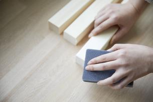 角材をヤスリで削る女性の手元の写真素材 [FYI04841373]
