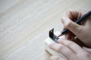 角材にL字金具を当てて印をつける手元の写真素材 [FYI04841375]