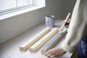 角材を塗装する女性の写真素材 [FYI04841377]