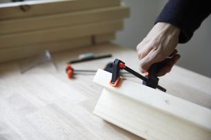 F型クランプで角材を留める男性の手元の写真素材 [FYI04841382]