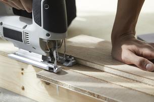 ジグゾーで木材を切る男性の手元の写真素材 [FYI04841389]