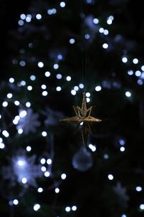 光の中に浮かぶゴールドの星のオーナメントの写真素材 [FYI04841393]
