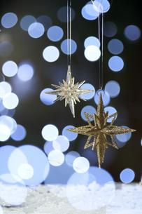 光の球とゴールドの大小二つの星のオーナメントの写真素材 [FYI04841409]