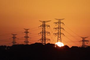 高圧線鉄塔群に沈む夕日の写真素材 [FYI04841553]