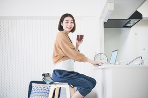 ドリンクを手にして在宅で仕事をする女性の写真素材 [FYI04842507]