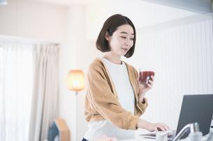 ドリンクを手にして在宅で仕事をする女性の写真素材 [FYI04842509]