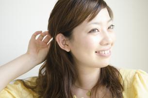 髪を触って笑っている女性の写真素材 [FYI04842559]