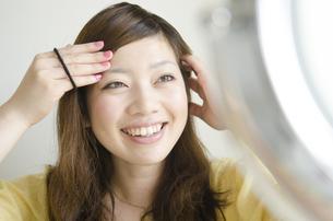 鏡を見ながら笑っている女性の写真素材 [FYI04842564]