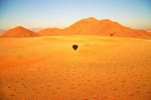 ナミブ砂漠に点在する謎のフェアリーサークルと気球の影の写真素材 [FYI04842643]