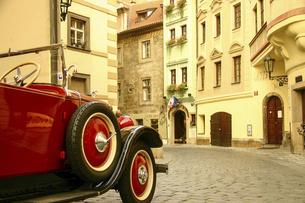 プラハ旧市街の路地と赤いクラシックカーの写真素材 [FYI04842681]