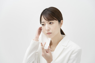マスクを着ける白いスーツ姿の女性の写真素材 [FYI04843208]