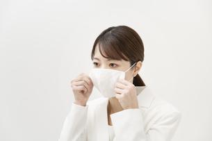 マスクを着ける白いスーツ姿の女性の写真素材 [FYI04843209]