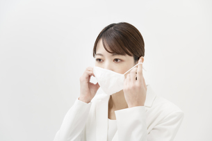 マスクを着ける白いスーツ姿の女性の写真素材 [FYI04843210]