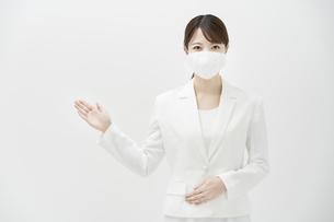 マスクを着けた白いスーツ姿の女性の写真素材 [FYI04843212]