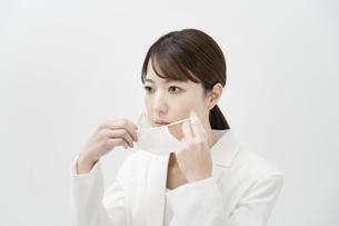 マスクを着ける白いスーツ姿の女性の写真素材 [FYI04843226]