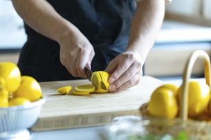 Man cutting lemons in kitchen.の写真素材 [FYI04843324]