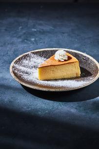 青いテーブルに乗ったチーズケーキの写真素材 [FYI04843509]