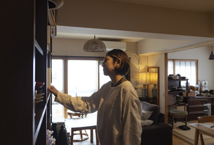 本棚の本を手に取る日本人女性の写真素材 [FYI04844693]