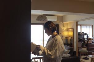 本棚の前で読書する日本人女性の写真素材 [FYI04844694]