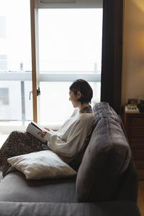 リビングで読書する日本人女性の写真素材 [FYI04844697]