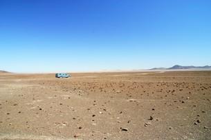荒涼とした大地をひた走る車の写真素材 [FYI04845575]