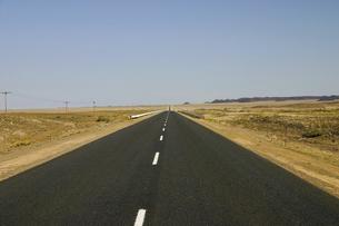 ナミブ砂漠の地平線まで続く直線道路の写真素材 [FYI04845597]