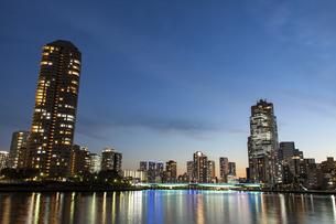 夕暮れの隅田川に反射する佃大橋と高層ビルの光の写真素材 [FYI04845614]