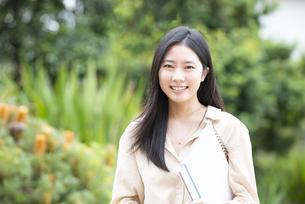 ノートを抱えて笑っている女性の写真素材 [FYI04847134]
