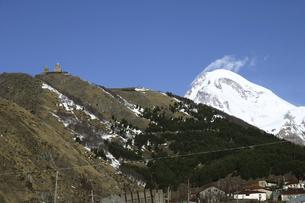 丘の上に建つゲルゲティ三位一体教会と雪を頂くカズベク山の写真素材 [FYI04848241]