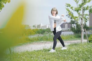 屋外で柔軟体操をする女性の写真素材 [FYI04848624]