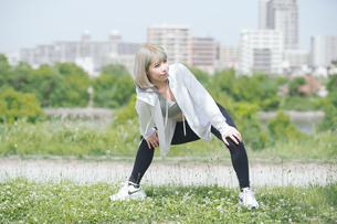 屋外で柔軟体操をする女性の写真素材 [FYI04848627]