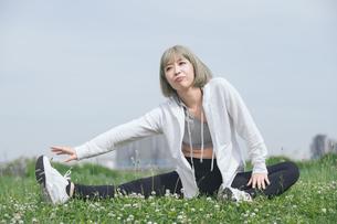 屋外で柔軟体操をする女性の写真素材 [FYI04848632]