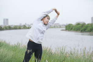 屋外で柔軟体操をする女性の写真素材 [FYI04848637]