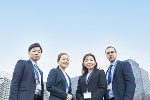 青空のもと、4人並ぶビジネスチームの写真素材 [FYI04848674]