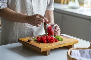 Man taking raspberries from jar at kitchen.の写真素材 [FYI04849361]