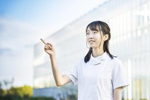指差しポーズをする白衣の女性の写真素材 [FYI04849623]