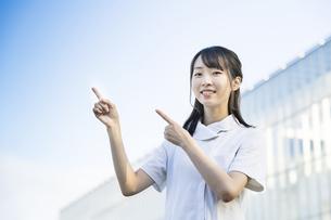 指差しポーズをする白衣の女性の写真素材 [FYI04849624]